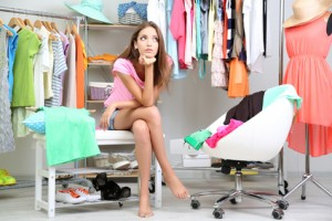 Beautiful girl thinking what to dress in walk-in closet
